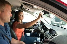 Student driver adjusting rear-view mirror with Instructor in car