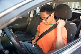 Student driver putting on seat belt