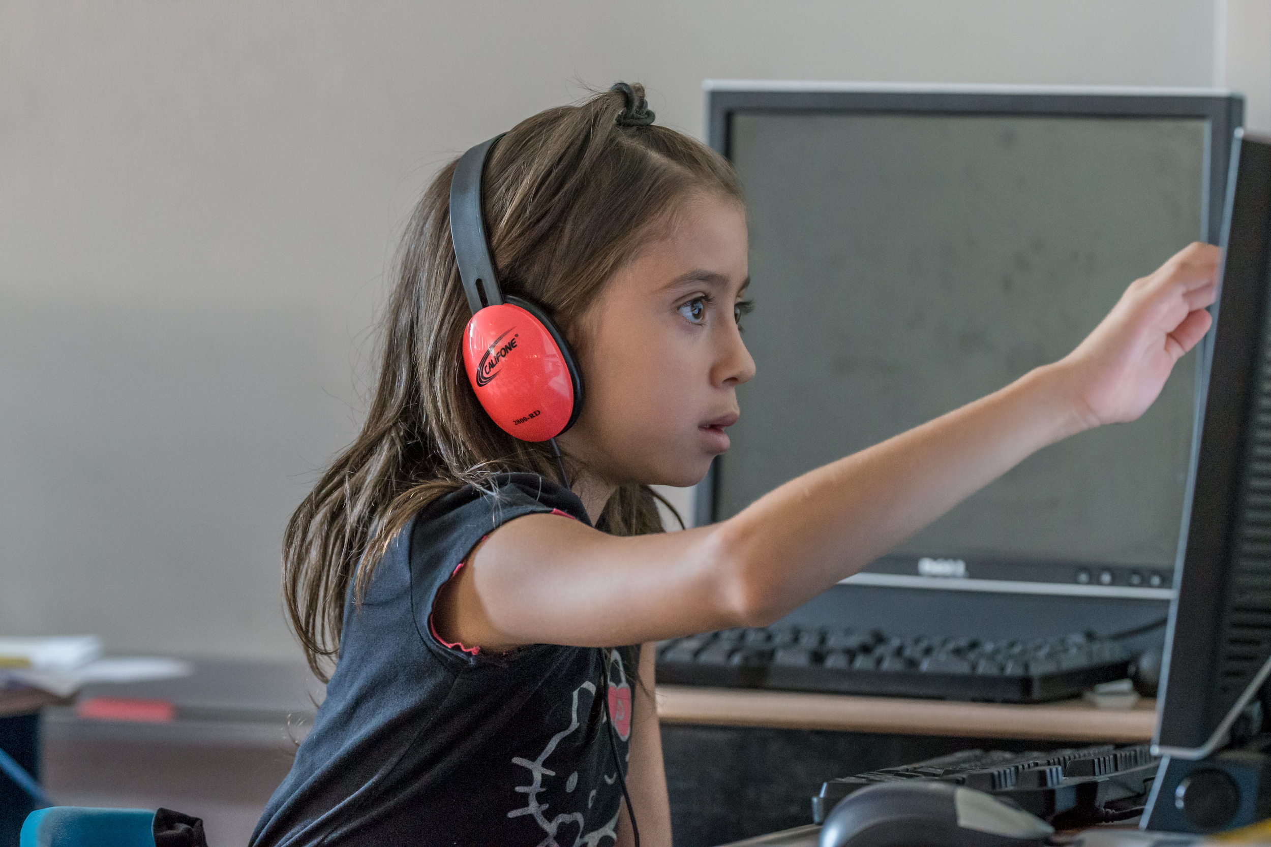 Child with headphones interacting with computer