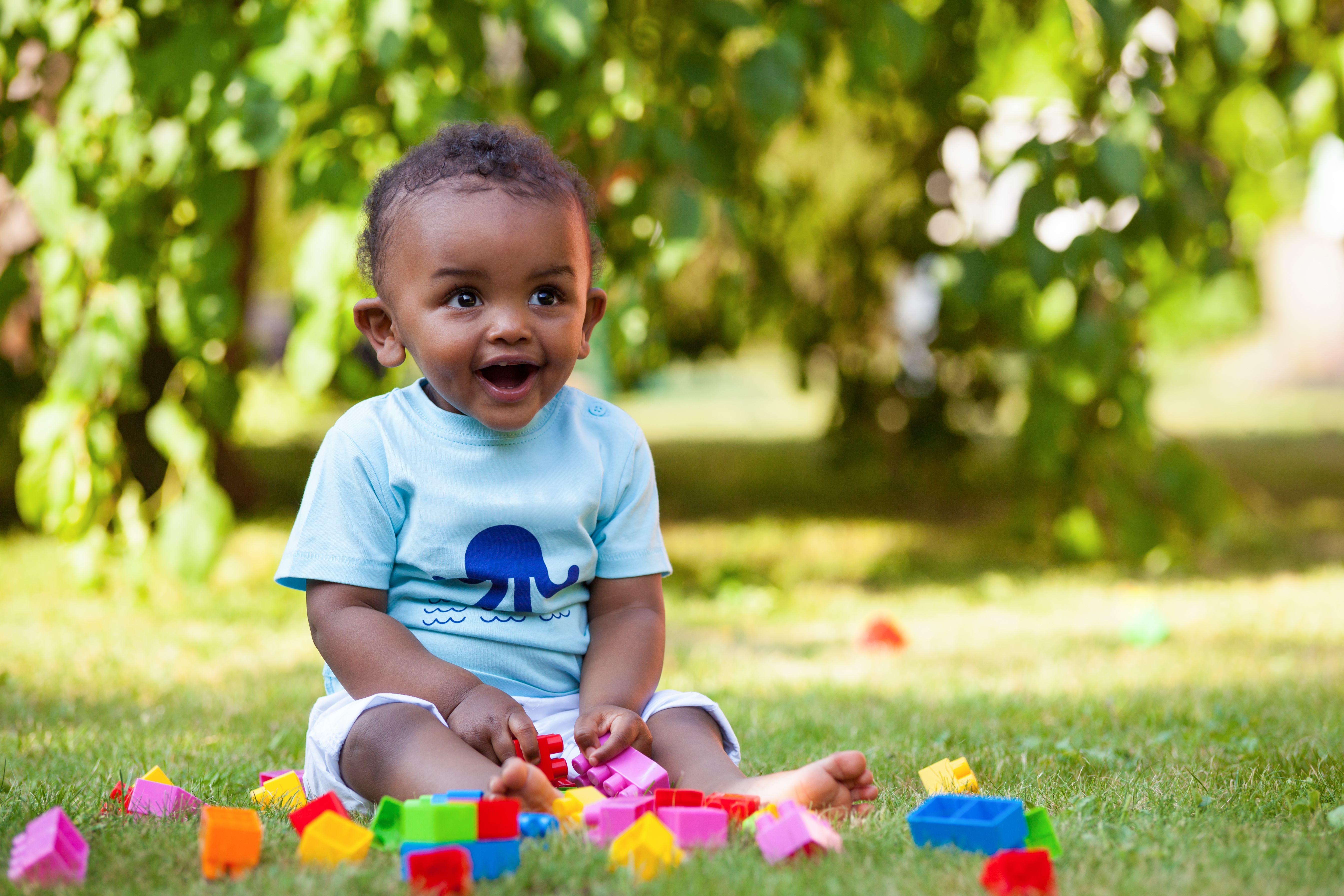 Smiling infant playing outside with blocks