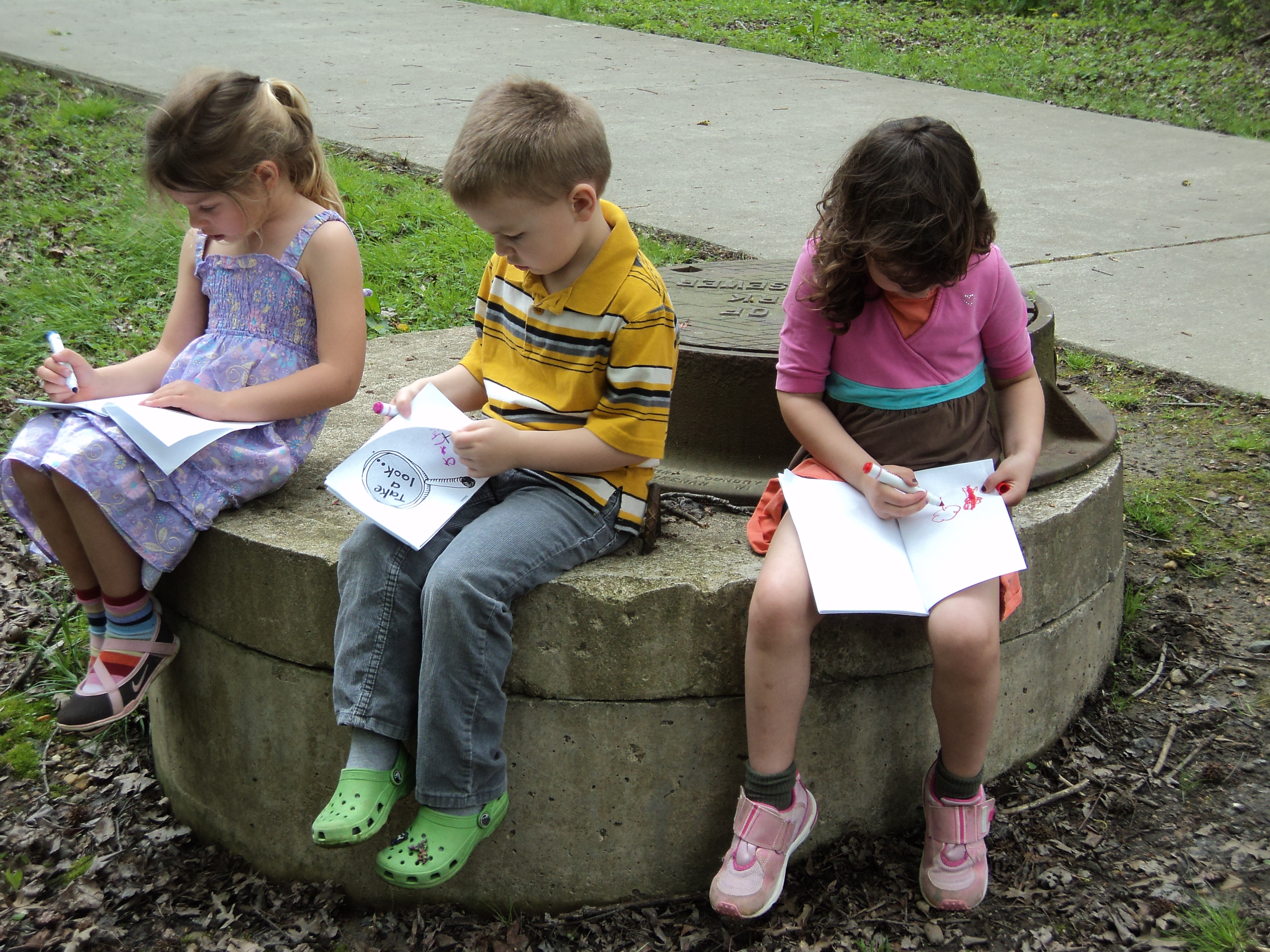 Children sitting outside coloring