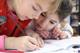 Two young girls concentrating on writing